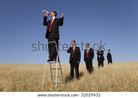 a group of businessman in the field getting in line for there time to speak