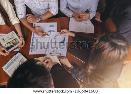 A group of businessmen meet to discuss the situation of marketing in the office and have information sheets on the table. Selected focus. Top view #1066841600
