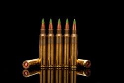 A group of 5.56 calibar, green tip bullets on black background
