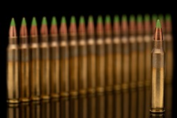 A group of 5.56 calibar, green tip bullets ordered into the line on black background
