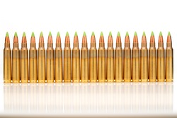 A group of 5.56 calibar, green tip bullets ordered into the line on white background
