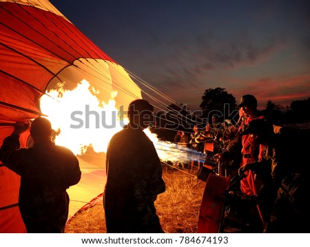 A group of Cambodian men inflating a hot air balloon in preparation for a tourist activity hot air balloon ride in Siem Reap Cambodia with Angkor Air