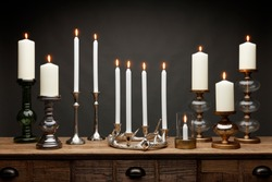 A group of candle sticks and candle holders and glowing candles, shot on a wooden table, with a dark grey background