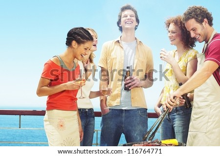 A group of casual young university students enjoying a barbecue down at the seaside