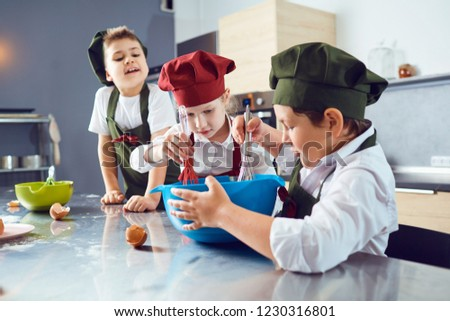 A group of children are cooking  in the kitchen.