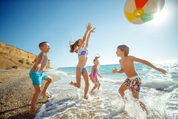A group of children have fun playing at the sea. Children in bathing suits. Friends holding hands and running on the beach. High quality photo.