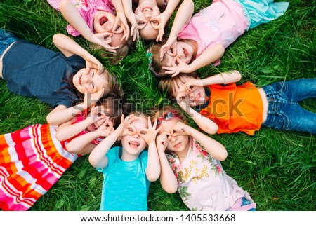 A group of children lying on the green grass in the Park. The interaction of the children #1405533668