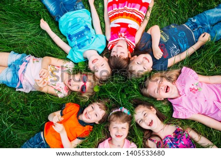 A group of children lying on the green grass in the Park. The interaction of the children #1405533680