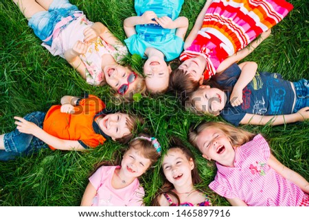 A group of children lying on the green grass in the Park. The interaction of the children #1465897916