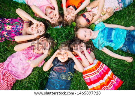 A group of children lying on the green grass in the Park. The interaction of the children #1465897928