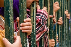 A group of children's sore hands grab on to metal bars. child exploitation, immigration, abuse, human trafficking, suffering concepts apply