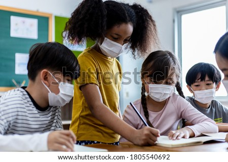 A group of Children students wearing medical masks in the classroom. An Asian woman teacher and students were discussing the lesson. Concept of prevention of the coronavirus outbreak And new normal