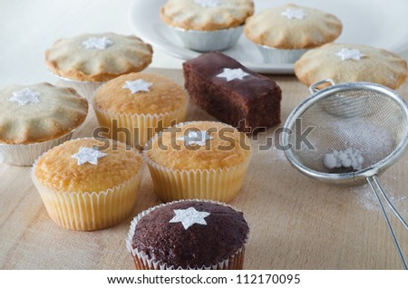 A group of Christmas cakes and mince pies, decorated with star shapes from sifted icing sugar, on a wooden chopping board with plate in background, and sifter with scattered icing sugar to the right.