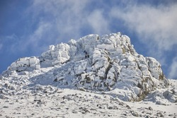 A group of climbers climb some icy rocks at the peak of La Naranja, in the Sierra de Guadarrama National Park. Madrid's community. Spain