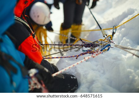 A group of climbers on a snow-covered mountain slope secured on a safety rope. Climbing station. Tilt-shift effect. #648571615