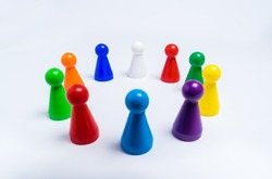 A group of colored pawns for board games arranged in a circle on a white background