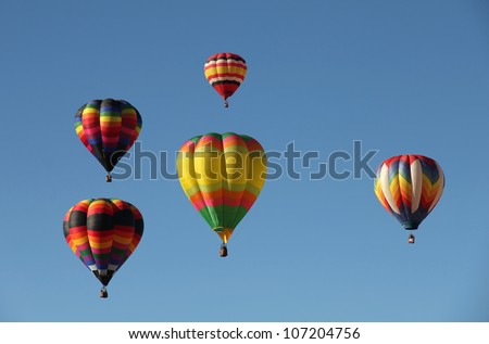 A group of colorful hot air balloons against a blue sky. Taken at the Albuquerque Balloon Fiesta in New Mexico
