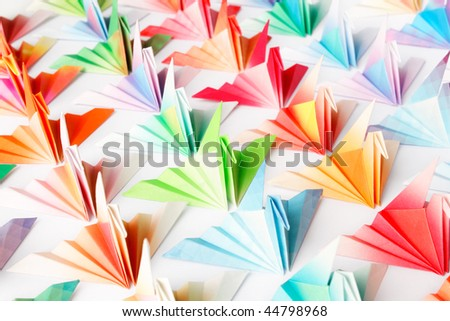 A group of colorful origami birds facing the same direction. High key soft focus.