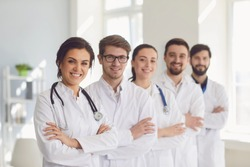 A group of confident practicing doctors in white coats are smiling against the backdrop of the clinic.