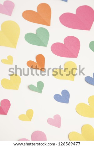 A group of cut out hearts from construction paper are arranged on a white background.