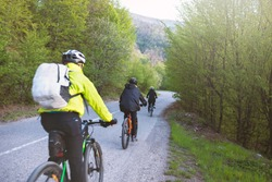 A group of cyclist ride bike in the jungle road,
