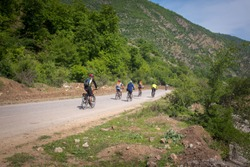 A group of cyclist ride bike in the jungle road, North of Iran.
