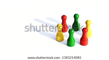 A group of different colored figures stands in a circle, through the light a shadow of each figure is thrown - concept to various groups #1383214085