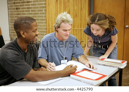A group of diverse adult education students going over an assignment.