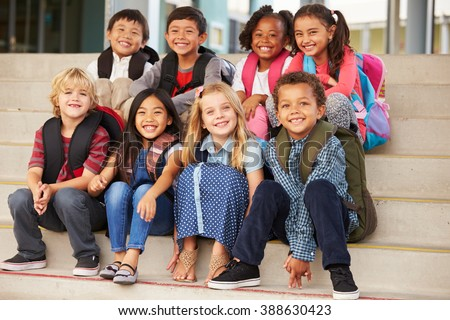 A group of elementary school kids sitting on school steps Stock photo ©