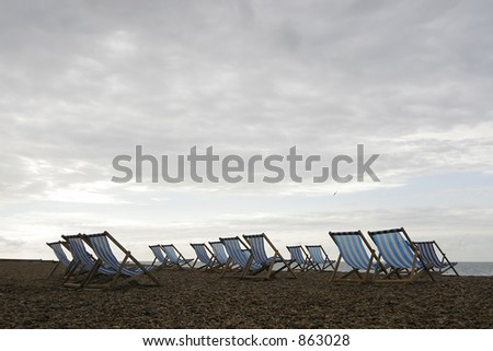 A group of empty deckchairs on a cloud covered beach in the early morning