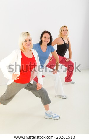 A group of exercising women. They're smiling and looking at camera.