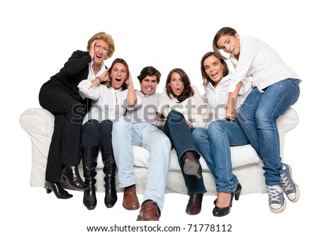 A group of family members sitting at home watching nervously TV