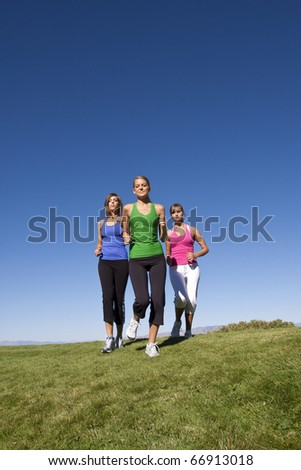 A group of female joggers running outdoors