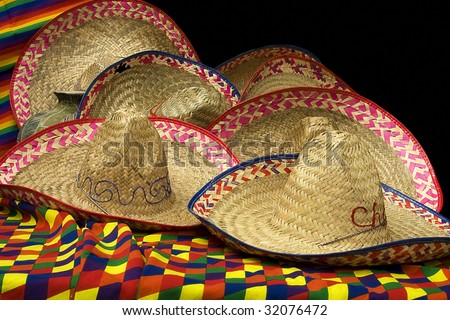 A group of festive Mexican hats on colorful material - stock photo