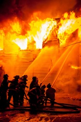 A group of firefighters use fire hoses to battle intense flames at major emergency fire that destroyed several buildings