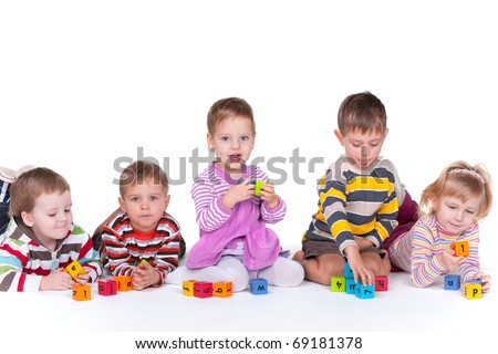 A group of five kids with different emotions are lying or sitting and playing colorful blocks; isolated on the white background