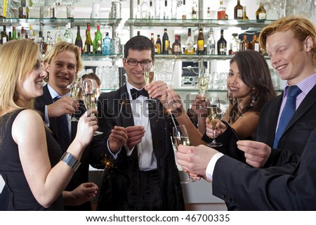 A group of five people celebrating new year at the bar in a club