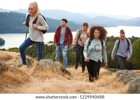 A group of five young adult friends smiling while hiking to a mountain summit
