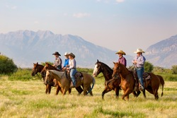 A group of five young people horseback riding in the grassy fields with the mountains of Utah in background