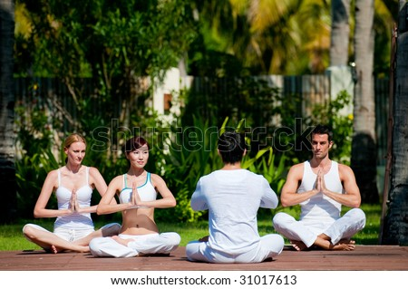 A group of four adults practising yoga outdoors - stock photo