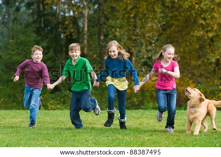 A group of four children holding hands and running together in a field.