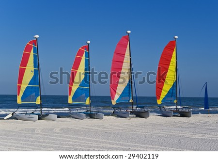 A group of four colorful catamaran sailboats on a tropical beach.