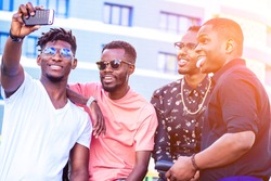 a group of four fashionable cool African American guys students communicating on the street looking at smartphone take pictures selfie on phone