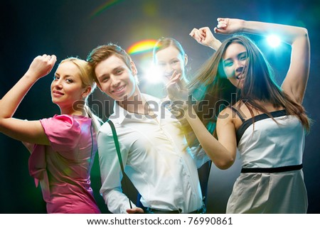 A group of four friends dancing and looking at camera