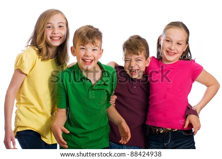 A group of four happy young kids wearing colorful shirts.