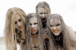 A group of four women are covered with mud  and dirt.Their hair is tangled in a mess. The facial  expression shows them to be unattractive and filthy.