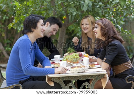 A group of four young friends enjoy a healthy snack and coffie at an outdoor restaurant