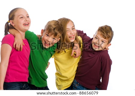 A group of four young kids wearing colorful shirts and having fun.