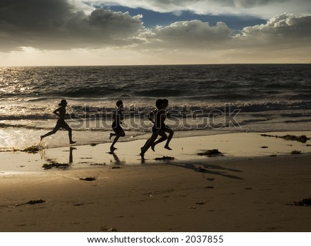 a group of four young men are jogging along the waters edge at the beach for exercise.