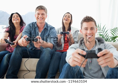 A group of friends enjoying a game together while looking into the camera